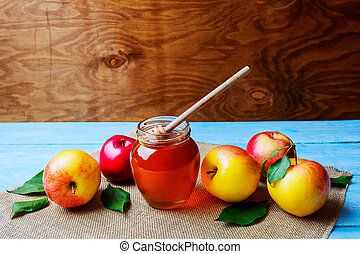 Honey glass jar and apples on rustic background copy space....