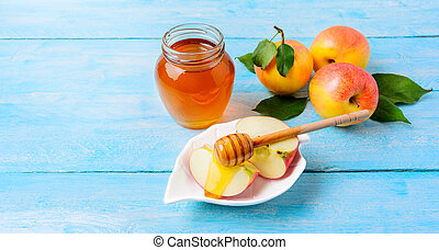 Honey jar and apple slices with honey on blue wooden...