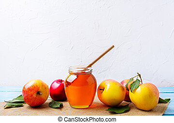 Honey jar with dipper and apples on white background. Rosh...