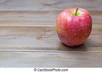 One apple on the wooden table