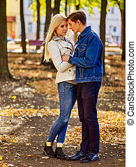 Young couple dressed in denim hugging and flirting in park....