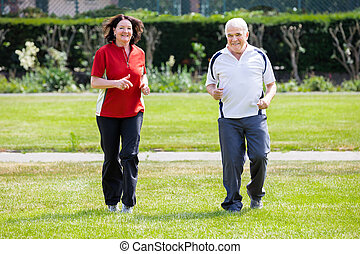 Couple Running In Park - Smiling Senior Couple Running...
