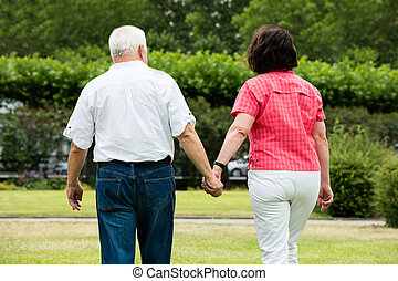 Couple Walking In Park - Rear View Of Senior Couple Walking...