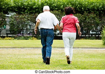 Couple Running Together In Park - Rear View Of Senior Couple...