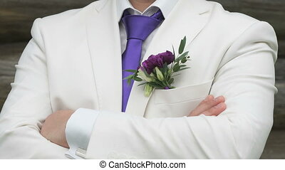 Man dressed in a white suit with purple tie outdoors