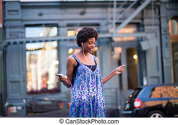 Portrait of fashionable black woman walking on city street and grooving to music