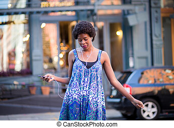 Portrait of fashionable black woman walking on city street and smiling grooving to music