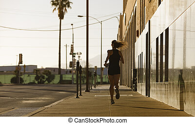 Woman out for a morning run - Woman running down a city...