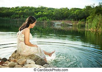 girl splashing water of lake