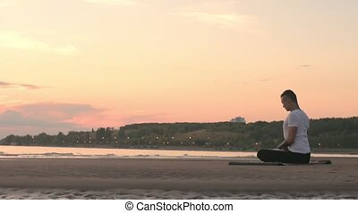 Tattoo man sitting on the beach in yoga lotus pose - Young...
