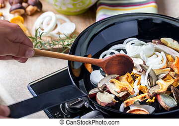 Frying pan with boletus, chanterelle and onion Cooking...