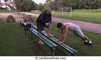 Young athlete do push ups near trainer on stadium