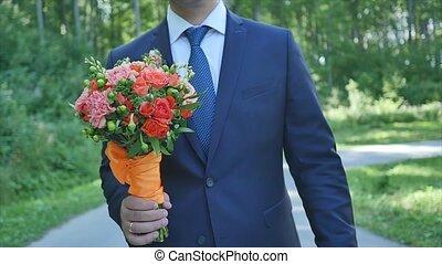 groom with orange bouqet walk.