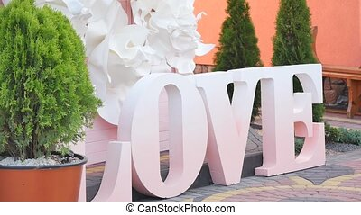 Love word outdoors. Big white plastic letters wedding...
