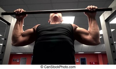 athlete pulls on the bar at the gym