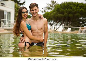 Young couple having fun - Young couple inside the pool and...