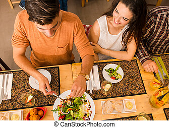 Happy couple at the restaurant and being served of food in...