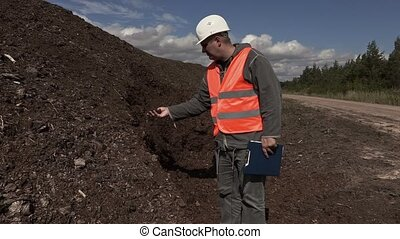 Engineer at pile of peat
