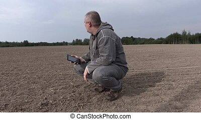 Farmer on the field check the soil and talking on the...