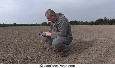 Farmer on the field check the soil and using tablet PC