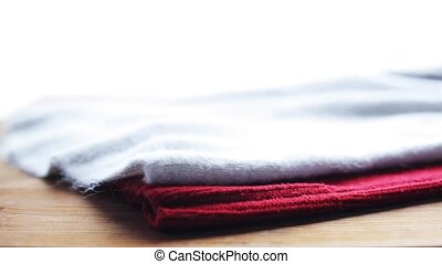 knitwear or woolen clothes on wooden table at home -...
