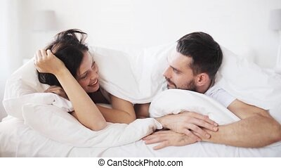 happy couple lying in bed at home - people, rest, love,...