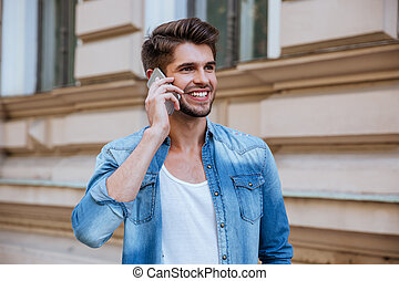 Smiling man standing on street and talking by cell phone -...