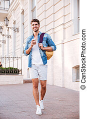 Man with backpack walking and drinking coffee in the city -...