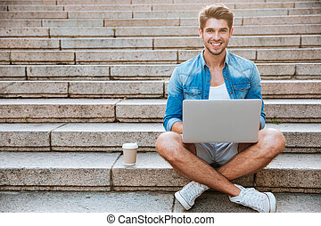 Man student using laptop while sitting on the staircase...
