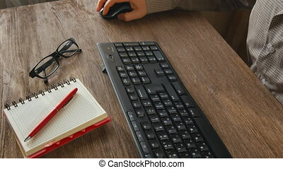 Man arms typing on keyboard at natural hardwood desk with...