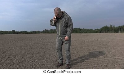Farmer talking on the smartphone and walking on the field
