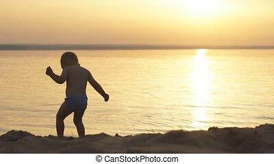Little boy on beach at sunset