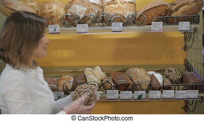 Woman puts black bread on the rack - Young caucasian woman...