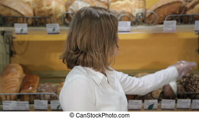 Female seller takes black bread from the rack - Young...