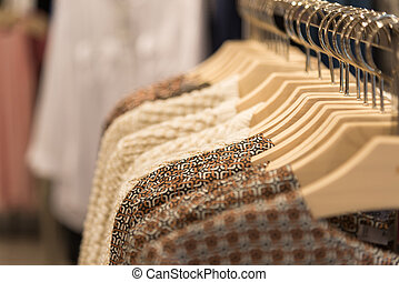 Womens clothes hanging on hangers in store - Womens clothes...