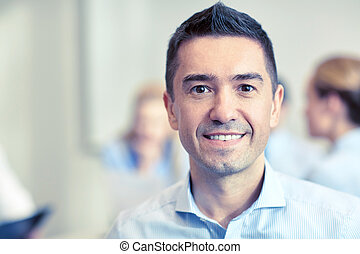 smiling businessman face in office - business, people and...