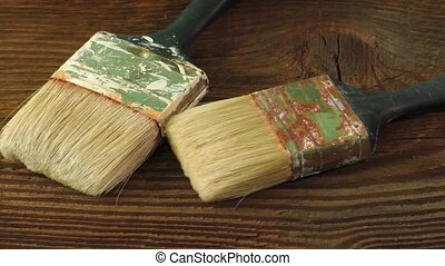 Old dirty paint brushes on a wooden rustic background