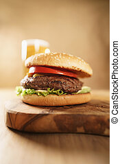 fresh juicy burger with lager beer on oak table, wide angle...