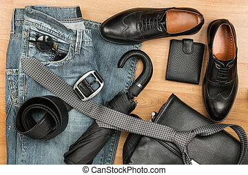Classic black shoes and men's clothes and accessories lie on the wooden floor