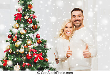 happy couple showing thumbs up with christmas tree - family,...