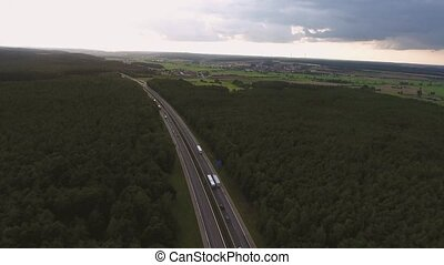 Aerial view of highway, forests and fields, village with...