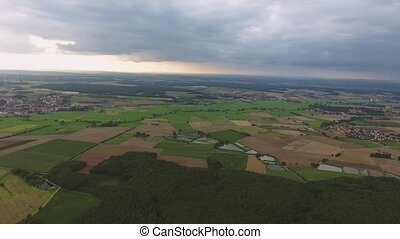 Aerial view of forests, fields, green grassland and villages.