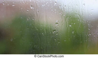 Rain and water drops falling on glass during rain storm,...