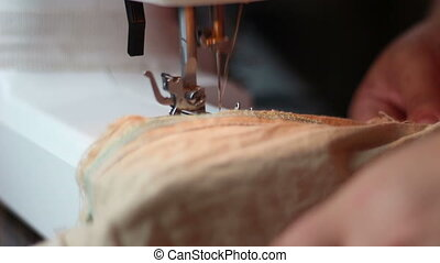 Close up shot of sewing machine sewing a light brown fabric....