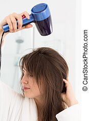 Trying her new hairdryer - Shot of a pretty young woman...