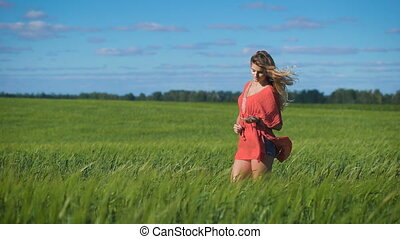 Charming blonde woman at a green field