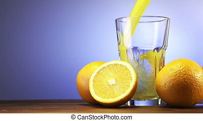 Orange juice pouring in glass on color background slow...