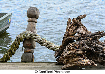 Rope knotted along a ship bollard. Docks with rope in...