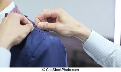 Tailor takes measurements from the mans jacket