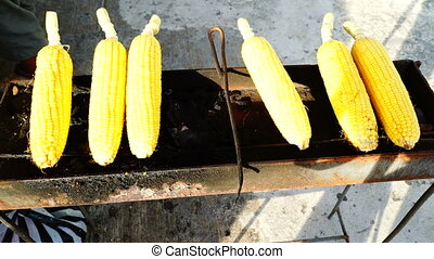 Cooking corn outside for sale.